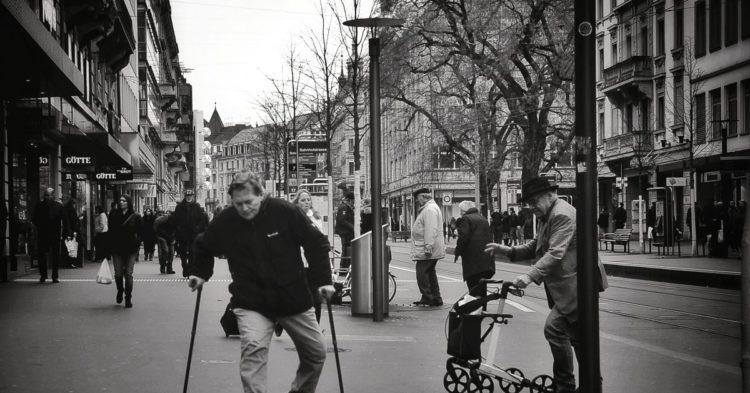 homme marche dans la rue avec des bequilles