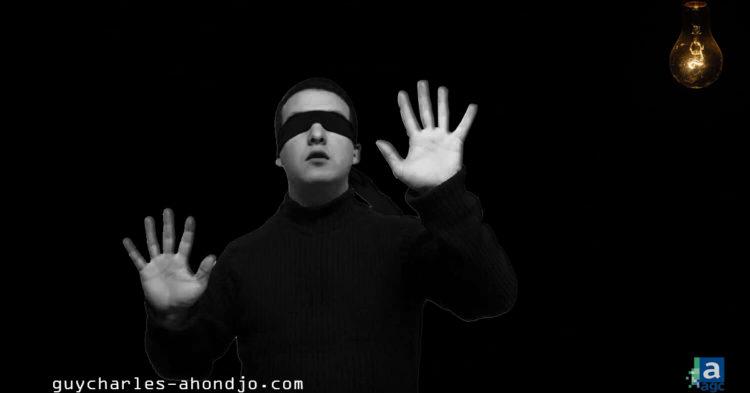 homme-portant-vetement-bandeau-noir-autour-des-yeux-cherche-ampoule-allumee